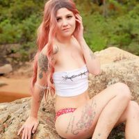 Beautiful redhead Canadian inked model Doriane Beaudin @dorianebeaudin at the beach for a hot summer photoshoot wearing a white and red bikini sitting on a rock showing her sexy legs brushing her red hair with her hand
