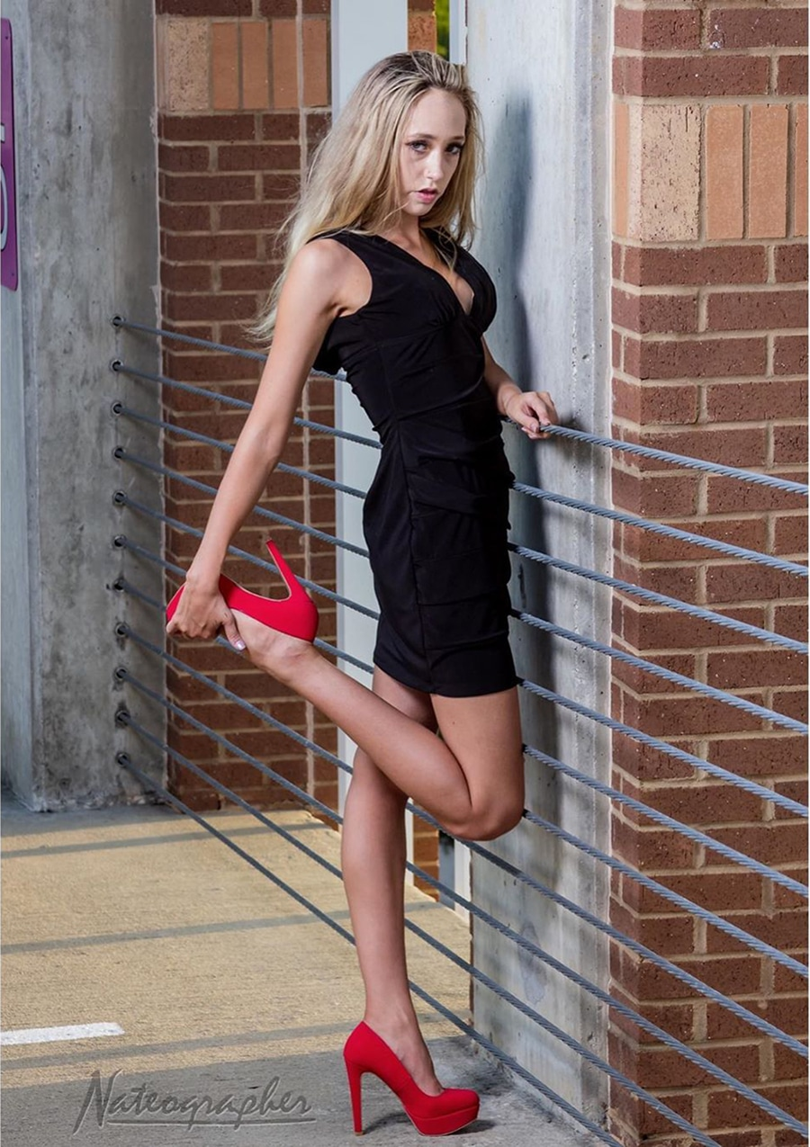 Beautiful young blonde model Alyssa Hensley @asap.ally wearing a short black dress with red high heels holding one feet in her hand giving a sexy look