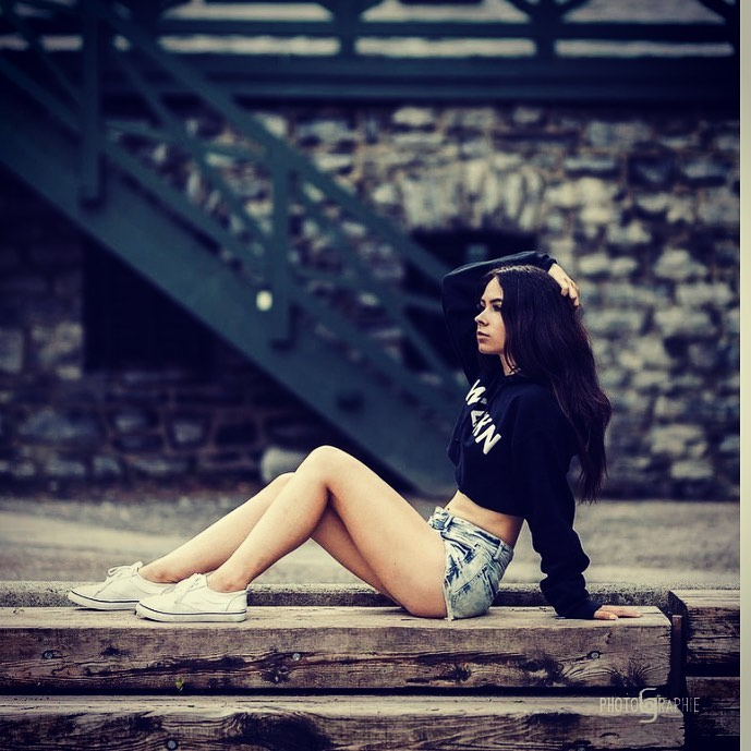 Beautiful Quebec model Samantha Neron @filledulac_xo wearing ripped denim short shorts with a crop black top and white sneakers sitting on the ground showing her bare legs