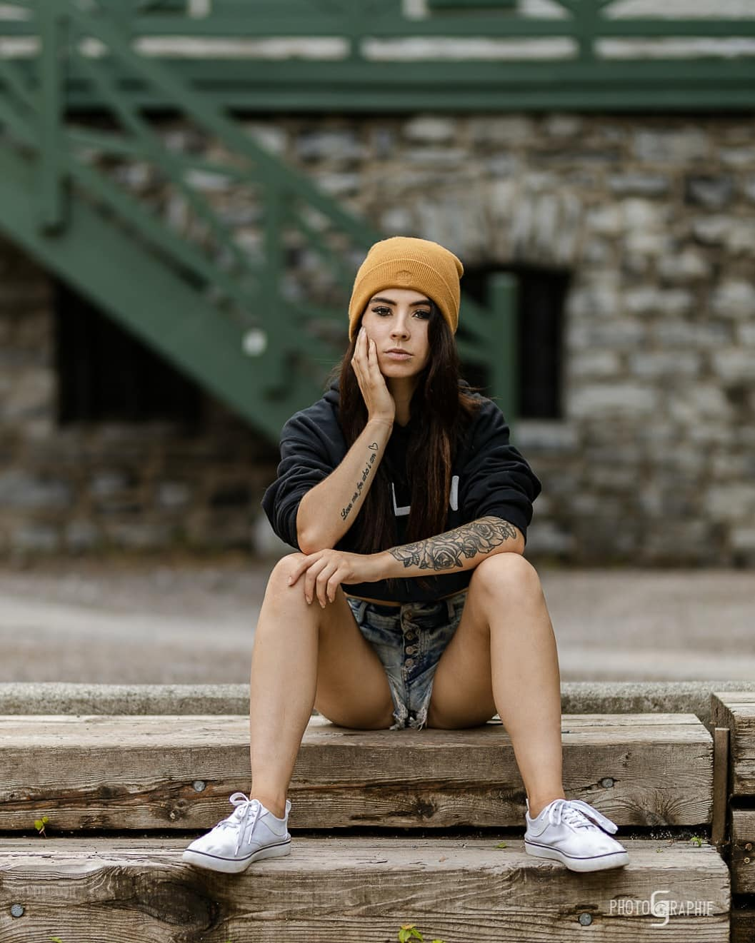 Beautiful tattooed French Canadian model Samantha Neron @filledulac_xo wearing ripped denim short shorts with a crop black top and white sneakers sitting with her sexy legs wide open