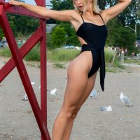 Young Canadian model McKenzie Lubeck @mckenzie.lubeck wearing a black Escape Swimwear swimsuit at the beach on a hot summer day hanging with both arms up at the lifeguard post showing her fit body and toned legs