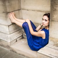 Beautiful young french model and actress Willow Kyle wearing a blue dress in Paris sitting on the ground with both bare legs up showing her feet and painted toe nails