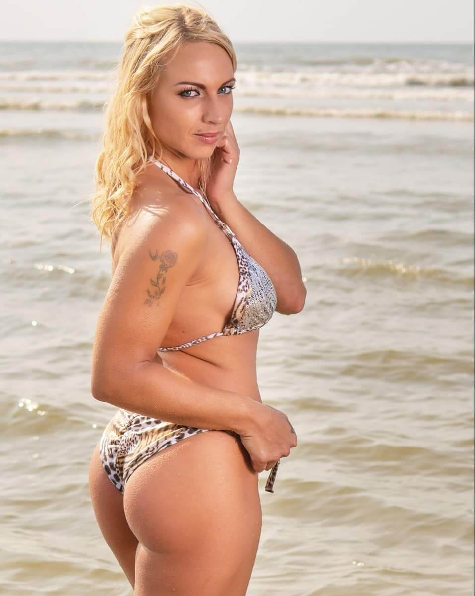 Beautiful inked Dutch fitness model Willeke Bartels @willekebartels.fitmodel at the beach on a sunny day wearing a silver white bikini looking over her shoulder showing her bare ass cheeks