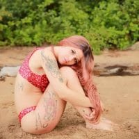 Beautiful tattooed young redhead Canadian model Doriane Beaudin wearing a red bikini for a summer beach photoshoot sitting in the sand holding her bare legs