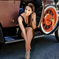 Beautiful French Canadian actress and tv personality Stephanie White wearing a black dress sitting with her long sexy legs crossed on a 1930 vintage car