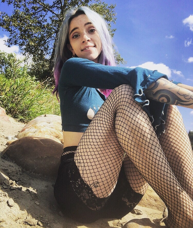 Beautiful Canadian alt queen Tora Reign @tora_reign outside wearing a long sleeves crop top, black shorts and fishnets nylons sitting on the ground showing her sexy legs
