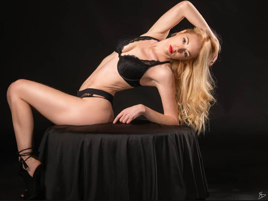 Beautiful blonde French model Fannysweet @fannysweet_and_gram wearing black lace lingerie with black high heels for a boudoir photoshoot leaning backward holding one arm up showing her sexy body, cleavage and legs