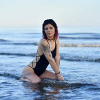 Beautiful Canadian model Doriane Beaudin wearing a black swimsuit and denim shorts at the beach