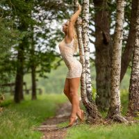 Beautiful Dutch model Willeke Bartels standing backed to a tree wearing a bikini with a transparent white cover-up