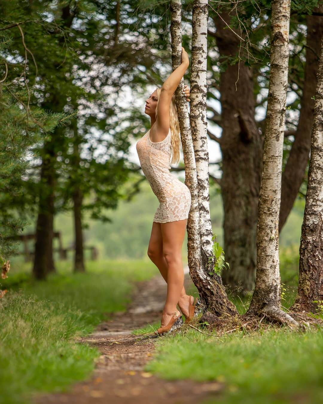 Beautiful Dutch model Willeke Bartels @willekebartels.fitmodel standing backed to a tree wearing a bikini with a transparent white cover-up holding her arms up showing her toned muscular and sexy legs