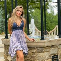 Beautiful American model Brittany Carr @brittanyacarr wearing a short blue dress in a lifetsyle photo shoot standing in front of aa wishing well showing cleavage with her sexy legs crossed