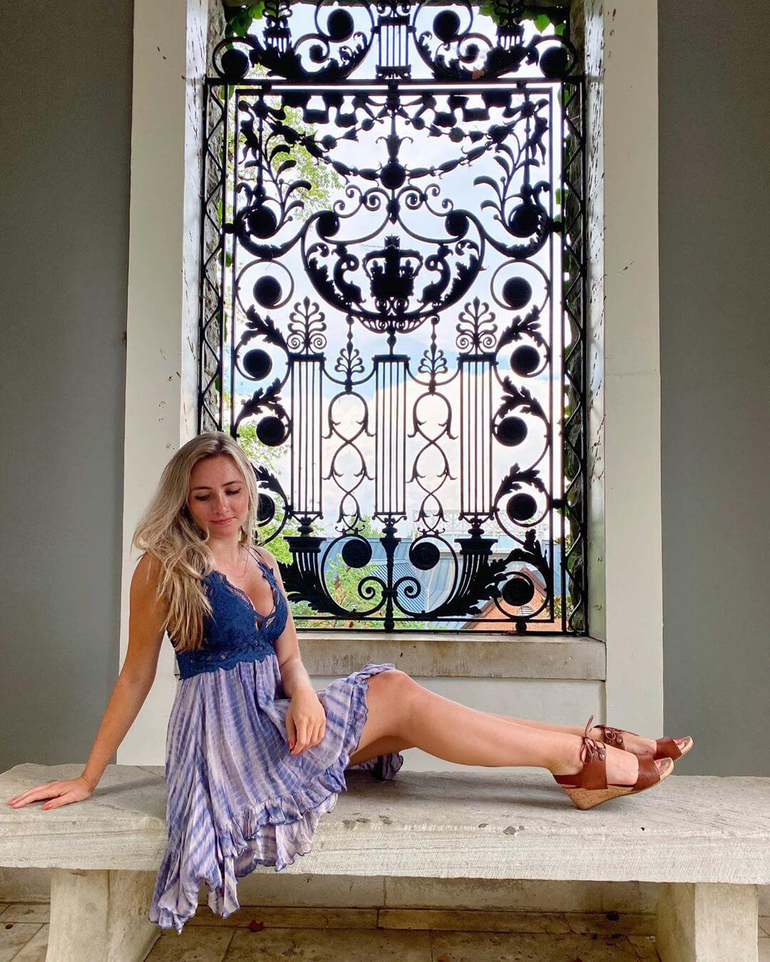 Beautiful American model Brittany Carr @brittanyacarr wearing a blue dress sitting in front of a vintage window showing her long sexy legs
