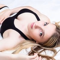 Beautiful young Russian blonde model Tatiana @tanya._.leonova wearing black Calvin Klein underwear lying in her bed giving a sexy look to the camera while showing cleavage