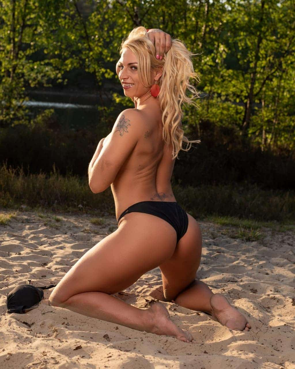 Beautiful Dutch fitness model Willeke Bartels @willekebartels.fitmodel kneeled in the beach sand smiling hith one arm up showing her bare feet and hot sexy body