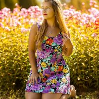 Beautiful blonde Canadian model wearing a colourful summer dress in a flower garden