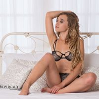 Beautiful hot blonde model Amber Mardynalka @modelamber_mardynalka wearing black lingerie sitting in a bed with her sexy legs open touching her bare feet with one arm up