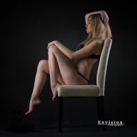Beautiful blonde model Amber Mardynalka @modelamber_mardynalka wearing black lingerie sitting on a chair in a boudoir photo session showing her sexy legs and bare feet