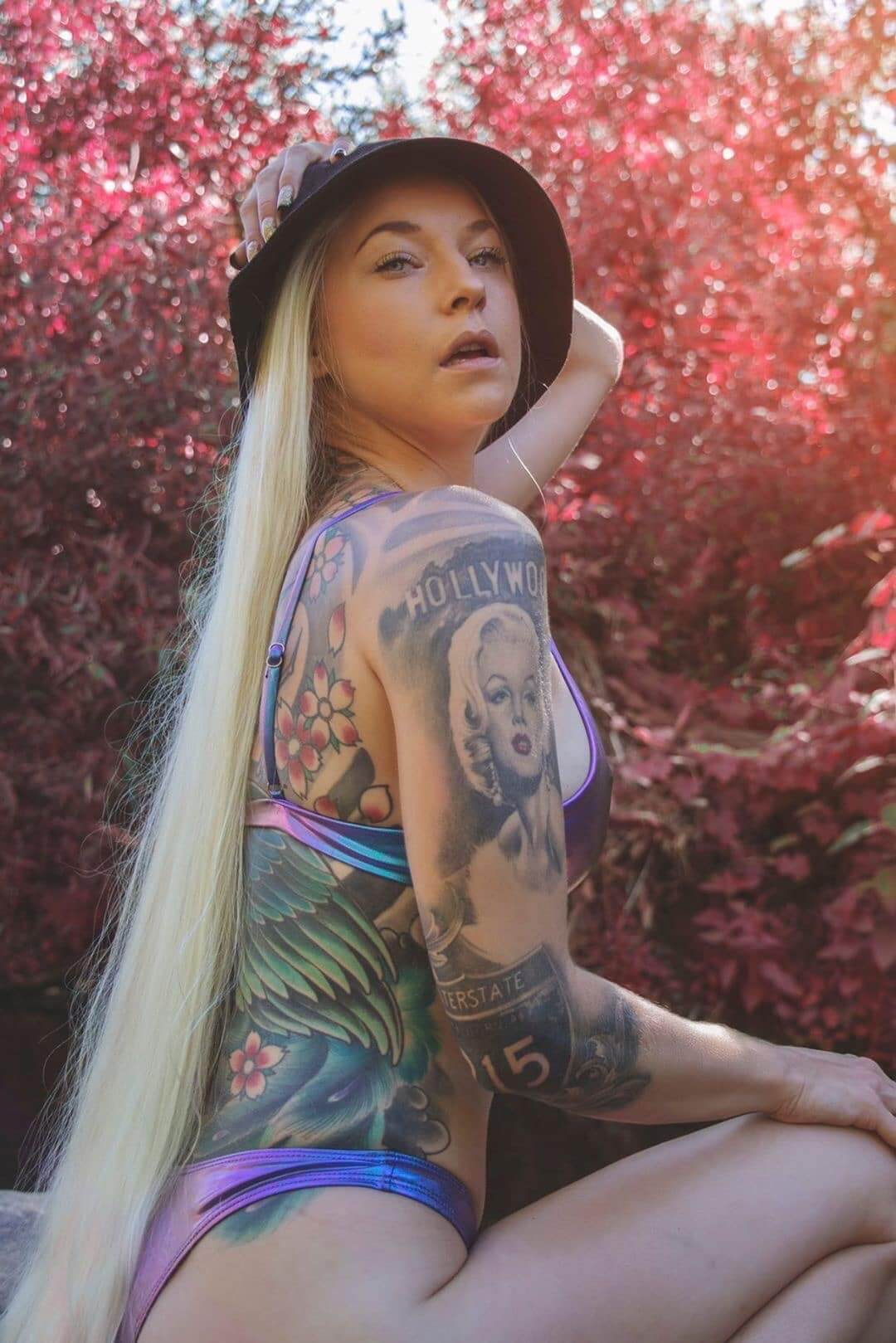 Beautiful blonde inked model Shayna Miller @its.shaynamiller wearing a multicolour bikini for an outdoor photoshoot holding one arm up showing her fit body full of tattoos