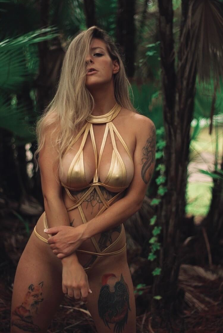 Beautiful inked model Stephenie Stombaugh @stombaugh_inspiration wearing a golden bikini leaning forward doing a sexy face white displaying her cleavage