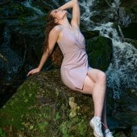 Beautiful model wearing a short dress and white sneakers for a nature photoshoot next to a waterfall