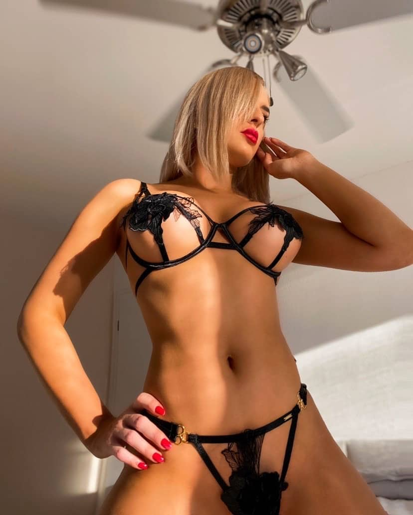 Beautiful blonde Munich model June Summers @june.summers.official wearing black revealing lingerie shot from below showing her tanned fit and sexy body and under boobs