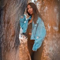 Beautiful young model Mia Zamudio 𝐌𝐢𝐚 𝐯𝐨𝐧 𝐒𝐜𝐡𝐨𝐛𝐞𝐫 wearing a denim jacket standing next to a tree in an autumn decor