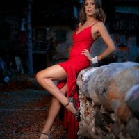 Beautiful Italian model and dancer wearing a red open dress and high heels