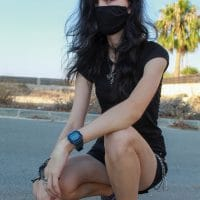 Beautiful photographer Beth @_nighthowler__ outside posing with a mask wearing short black shorts crouching in the street giving us a sweet look