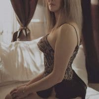 Beautiful model wearing lingerie sitting on her bare feet for a boudoir photo