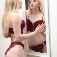 Beautiful russian model Tatiana @tanya._.leonova wearing red lingerie looking at herself in a mirror showing her fit body and booty in a boudoir session