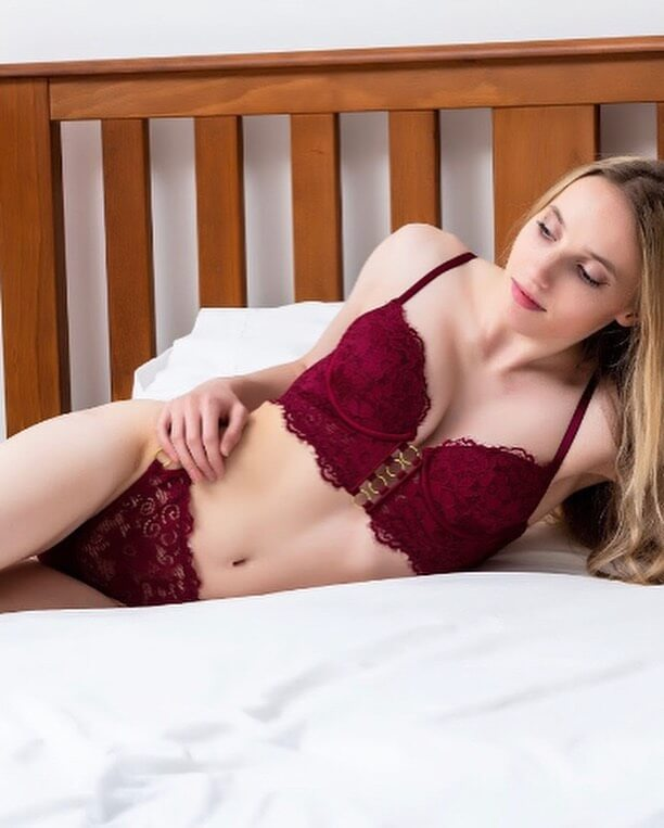 Beautiful blonde russian woman Tatiana @tanya._.leonova wearing red lingerie lying in a bed showing cleavage and fit abs in a boudoir session