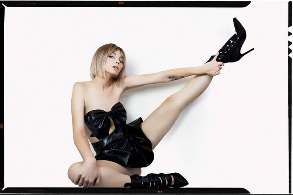 Beautiful American model Gooty @gootyxo wearing a short black latex skirt with a black crop top and high heels boots with her legs wide open holding one in the air letting us see her bare ass cheeks in a session by Portrait&Boudoir Photography @shotsfiredphotostyling