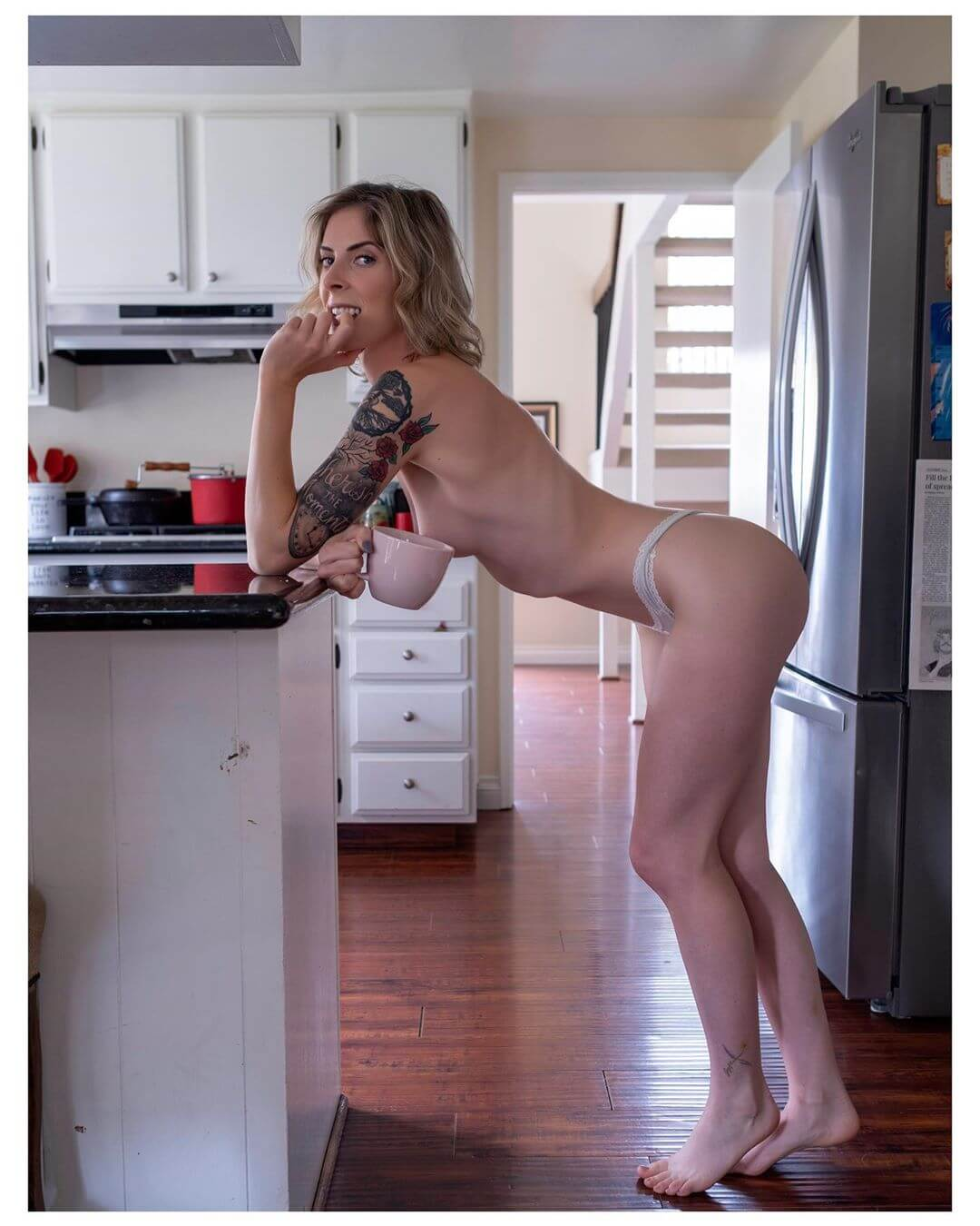 Beautiful blonde American model Cherish @cherishthemodel in the nude barefoot in a kitchen hiding her bare breast with a coffee mug biting her finger showing her perfect fit body and sexy legs for a boudoir photo session