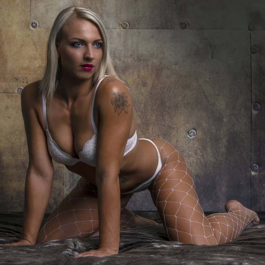 Beautiful Blonde tattooed Dutch model Willeke Bartels @willekebartels.fitmodel wearing white lingerie and nylons fishnets kneeling on the ground showing her fit body and cleavage in a boudoir photo session