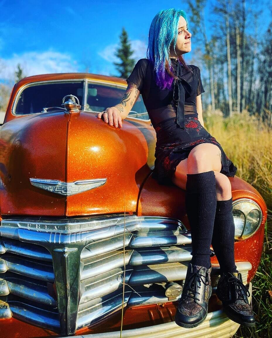 Beautiful blue hair inked Canadian alt model Tora Reign @tora_reign wearing a short black dress and black shoes sitting on a vintage orange Chevrolet car with her legs crossed