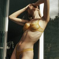 Beautiful French model wearing yellow lace lingerie holding her arms up by the window
