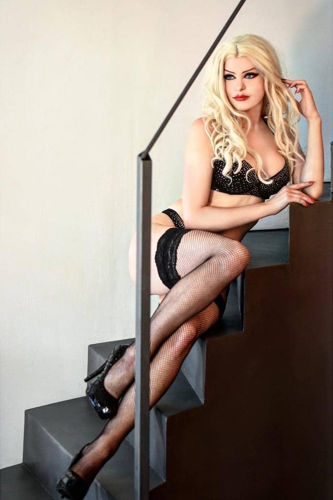 Beautiful blonde dominatrix model Michaela Fame Style @modelmichaelafamestyle wearing black lingerie, fishnets and high heels sitting in the stairs showing cleavage and her long sexy legs