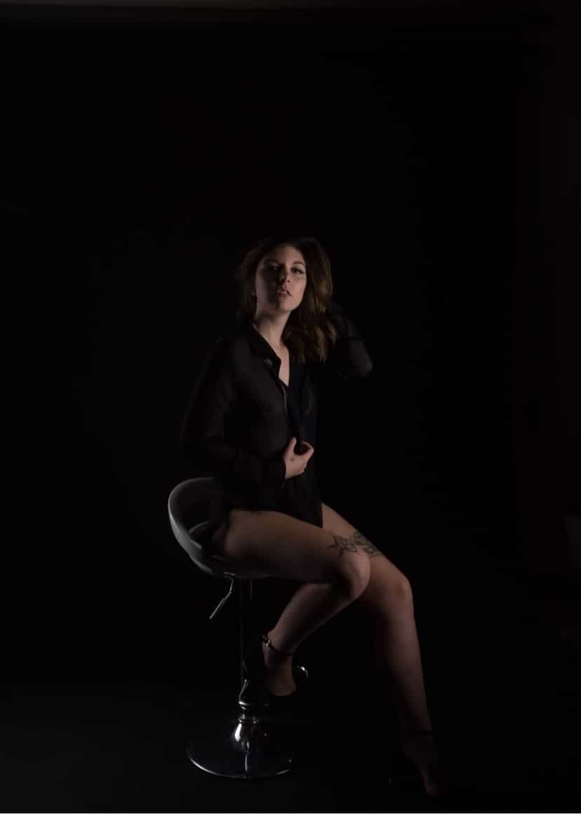 Beautiful tattooed young Canadian model Carolanne Bergeron @carolanne.bergeron wearing a see through black shirt and high heels showing her long sexy legs in a dark boudoir session
