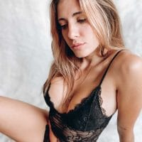 Beautiful Argentine model Camila Sol Botti @csbotti wearing ᴄᴀʀᴀᴍᴇʟᴀs ʟɪɴɢᴇʀɪᴇ black lace top and black panties sitting on the floor showing her cute face, hot cleavage and perfect latina body