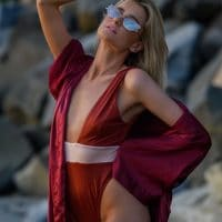 Beautiful SoCal blonde model Anastasiya Alekseyevna @princessa.anastasiya wearing a red swimwear holding one arm up showing her fit beach body