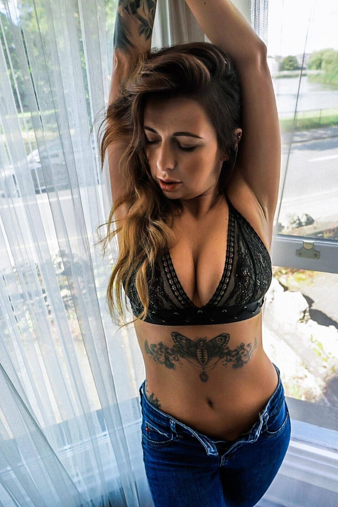 Beautiful tattooed model Anka Dawid @freakin.juicy wearing a black bra holding her arms up showing het fit mature body and massive cleavage