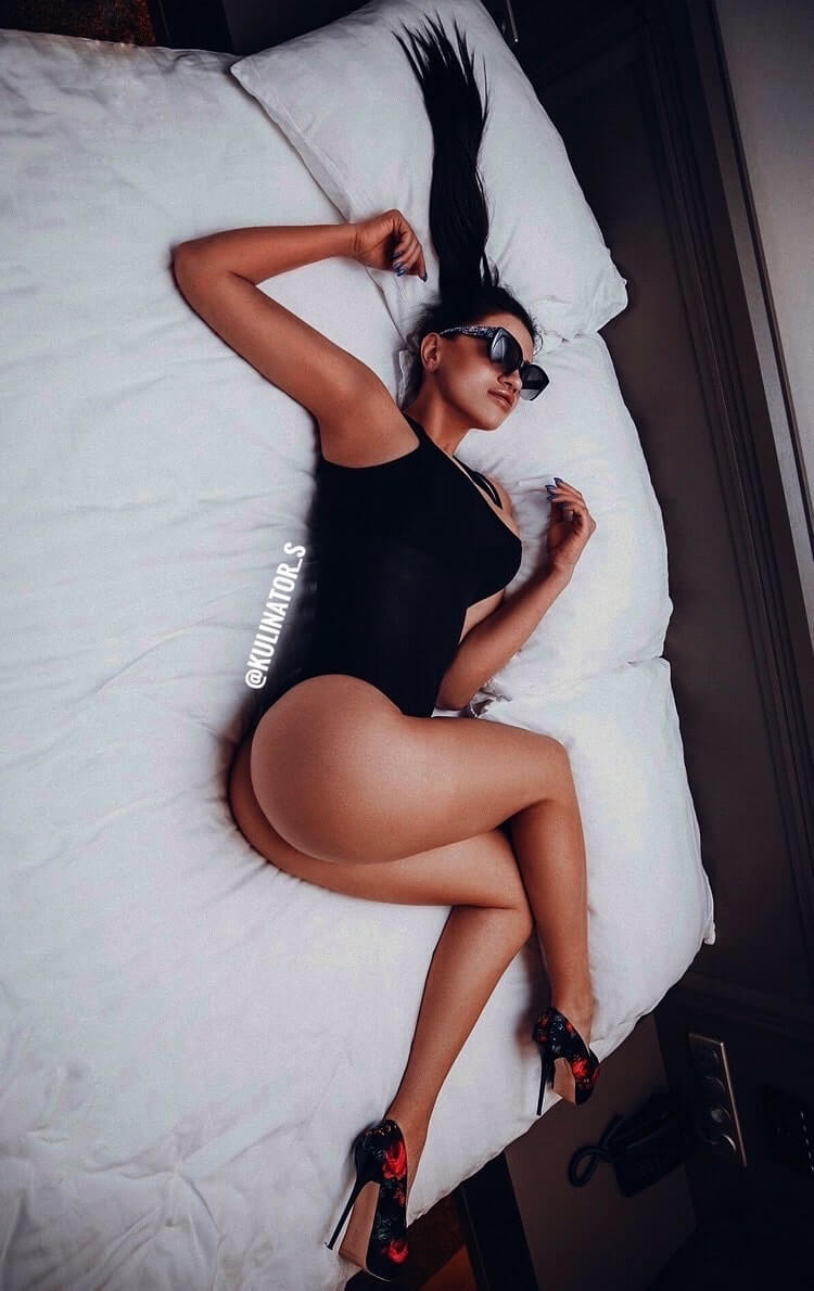 Beautiful model Kulina @kulinator_s lying in a bed wearing a black bodysuit and black high heels showing her fit body, hot booty and sexy legs