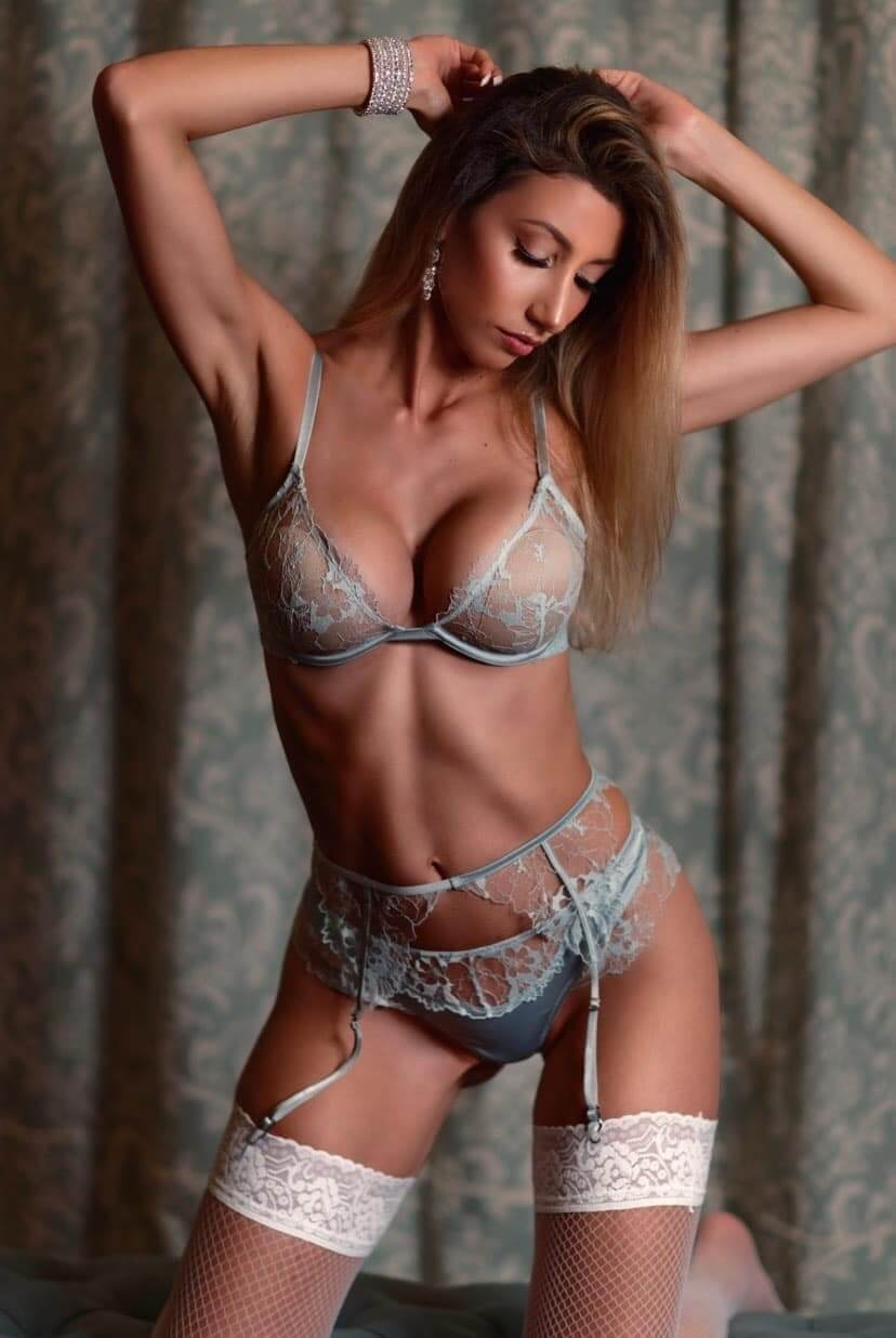 Beautiful American model Valerie8m @valerie8m wearing lingerie holding her arms up showing her fit body and massive cleavage in a boudoir photo session