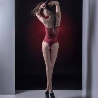 Beautiful Italian brunette model wearing red lingerie and black high heels in a boudoir session