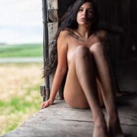 Beautiful Canadian model in the nude for an outdoor boudoir photo session on a freight train