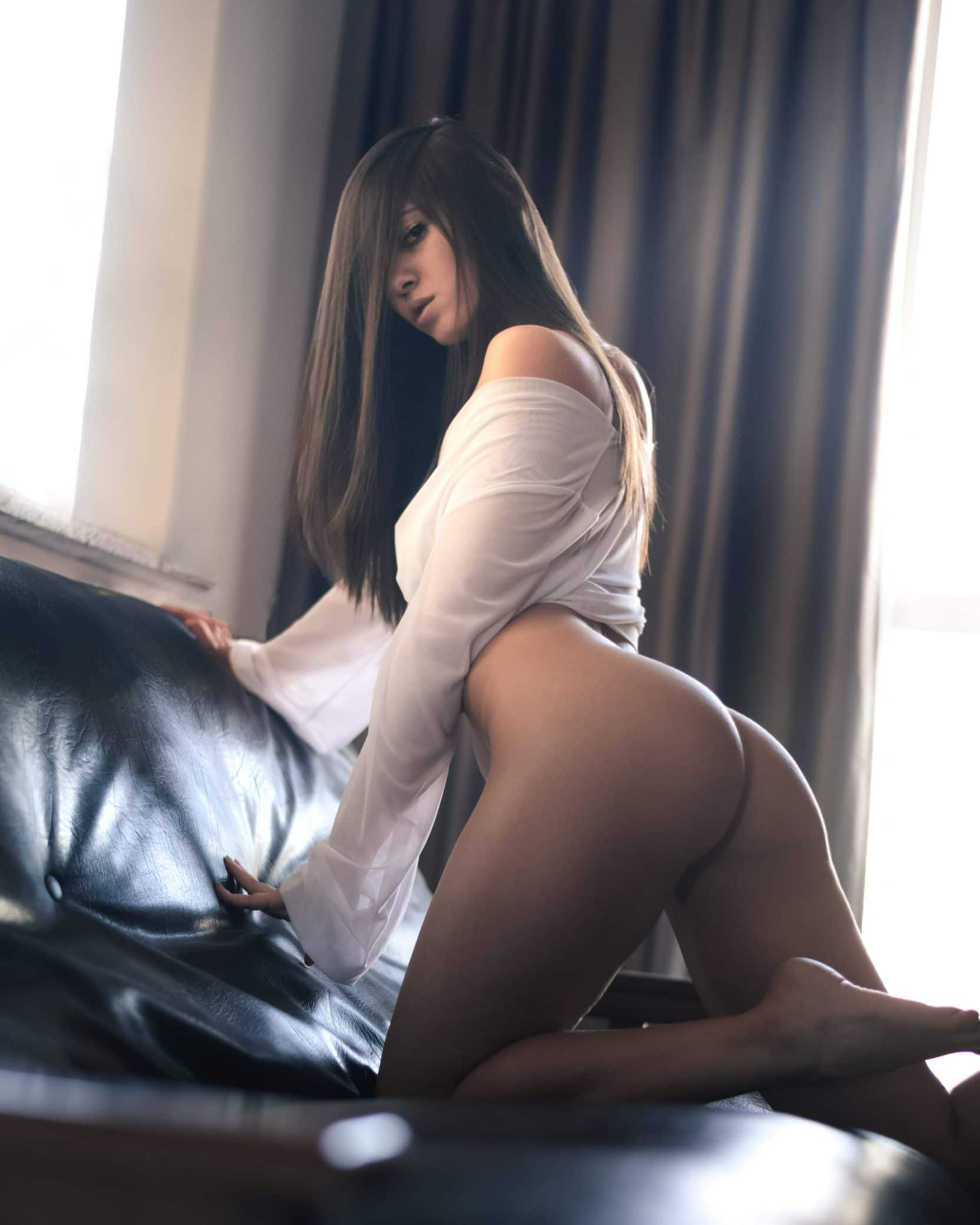 Beautiful Argentine model Micaela Ponce @miki.infinity only wearing a white shirt in a boudoir photoshoot kneeling nude booty showing her sexy legs and bare feet giving a sexy look