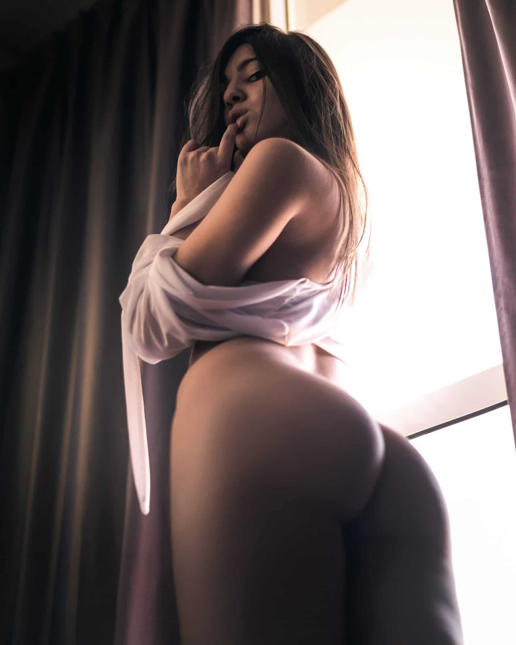 Beautiful nude Argentine model Micaela Ponce @miki.infinity only wearing a white shirt looking down showing her bare booty with her finger in her mouth in a boudoir photoshoot