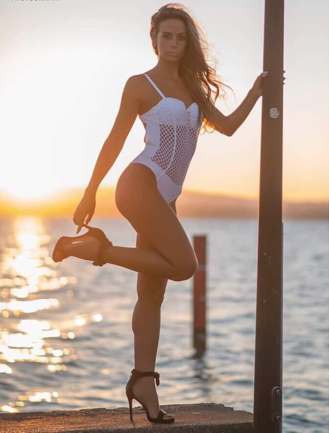 Beautiful Italian blonde model Laura Dotti @lauradotti17 standing holding her leg up in front of sunset