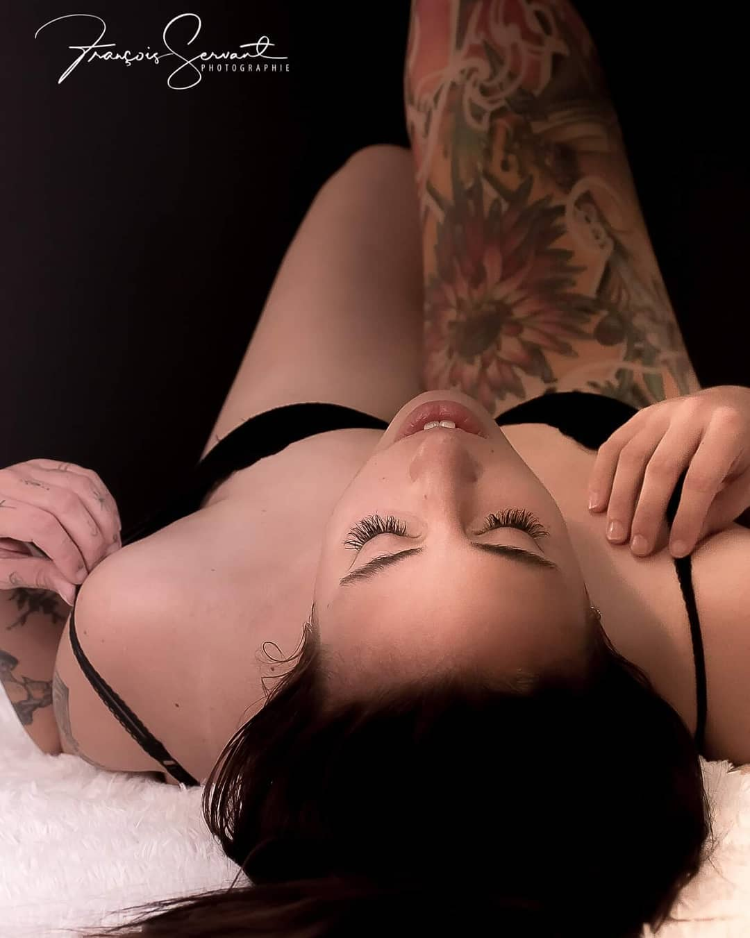 Beautiful Canadian model Stephanie Chouinard @stephaniechouinard lying on her back wearing lingerie showing her inked thigh in a boudoir photo session by photographer Francois Servant @photographie.frservant