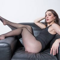 Sexy inked Canadian model Ashley Stevens @ashley.s.modeling sitting on a leather chair wearing a black leotard and nylon fishnets showing her long legs booty and feet
